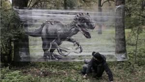Taiteilija tekee graffiteja metsään levitettyihin kelmuihin. Tässä tulos.