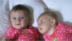 Äiti laittaa kaksoset vierekkäin sängylle. Seuraa oikeanpuoleista tyttöä.